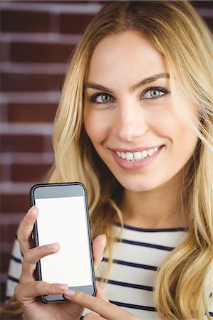 Woman holding her smartphone on brick wall Stock Photo - Premium Royalty-Free, Code: 6109-08435816