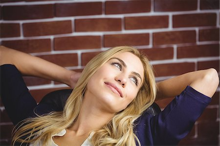 Blonde woman relaxing in chair on brick wall Stock Photo - Premium Royalty-Free, Code: 6109-08435820