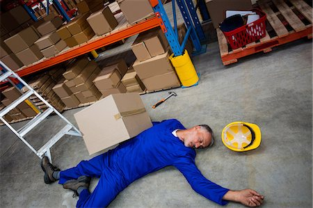dangerous accident - High angle view of unconscious worker lying on the floor Stock Photo - Premium Royalty-Free, Code: 6109-08581604