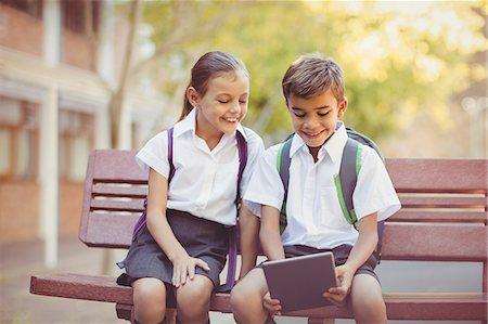 school girl uniforms - Happy school kids sitting on bench and using digital tablet Stock Photo - Premium Royalty-Free, Code: 6109-08581953