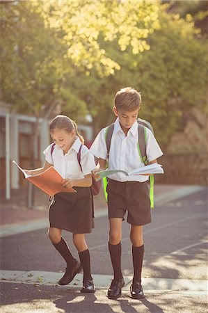 school - School kids reading books while walking in campus Stock Photo - Premium Royalty-Free, Code: 6109-08581956