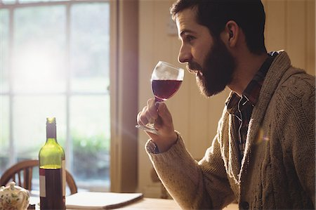 Profile view of hipster man examining glass of wine Stock Photo - Premium Royalty-Free, Code: 6109-08582064