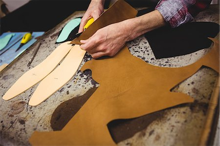 High angle view of cobbler cutting leather Stock Photo - Premium Royalty-Free, Code: 6109-08582143