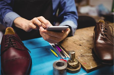 services - Close up of cobbler typing on his mobile phone Stock Photo - Premium Royalty-Free, Code: 6109-08582170
