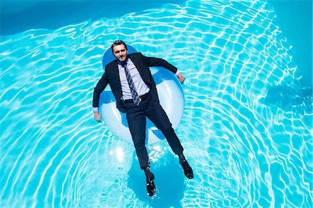 pool - Businessman relaxing on inflatable Stock Photo - Premium Royalty-Free, Code: 6109-08536443