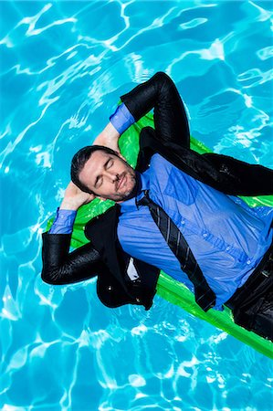 swimming - Businessman relaxing on inflatable Stock Photo - Premium Royalty-Free, Code: 6109-08536451