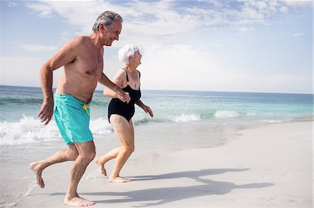 Senior couple holding hands and running on the beach Stock Photo - Premium Royalty-Free, Code: 6109-08536523