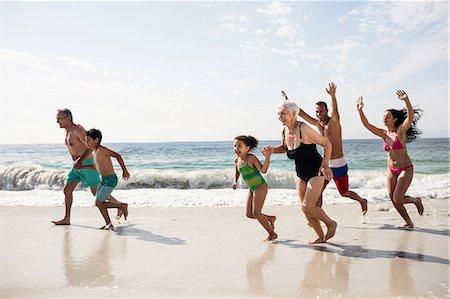 Happy family running on beach Stock Photo - Premium Royalty-Free, Code: 6109-08536526