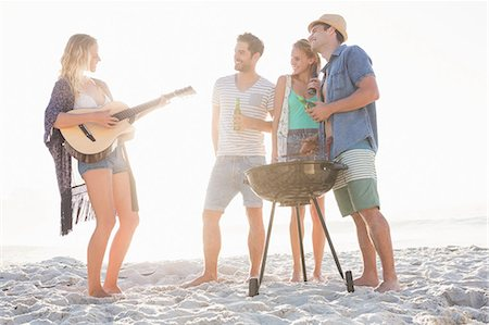 Cute group of friends having a barbecue and beers and playing the guitar Stock Photo - Premium Royalty-Free, Code: 6109-08536835