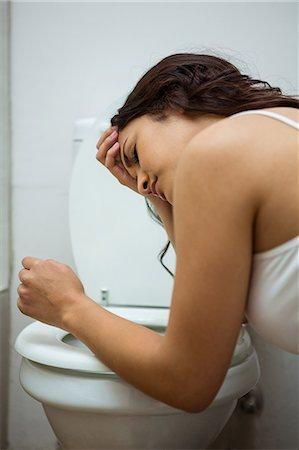 Young woman about to vomit into a commode toilet Stock Photo - Premium Royalty-Free, Code: 6109-08536958