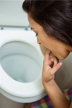 Young woman about to vomit into a commode toilet Stock Photo - Premium Royalty-Free, Code: 6109-08536960