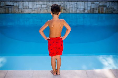 Shirtless boy standing in swimming pool Stock Photo - Premium Royalty-Free, Code: 6109-08537045