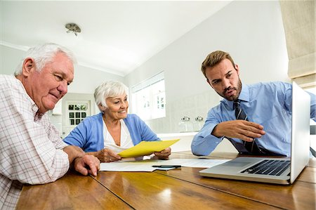 Agent suggesting senior couple on laptop at table Stock Photo - Premium Royalty-Free, Code: 6109-08537095