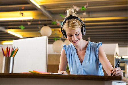 Graphic designer listening to headphones while using graphic tablet Stock Photo - Premium Royalty-Free, Code: 6109-08537184