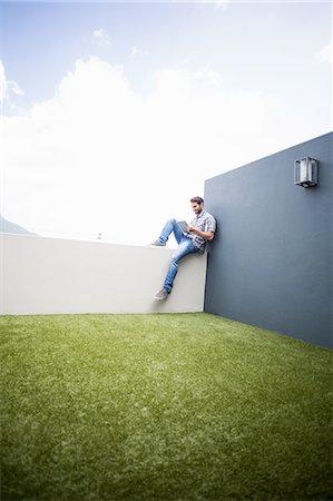 flat - Man sitting on terrace using digital tablet Stock Photo - Premium Royalty-Free, Code: 6109-08537127