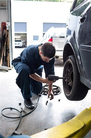 Mechanic changing car wheel with pneumatic wrench Stock Photo - Premium Royalty-Free, Code: 6109-08537665