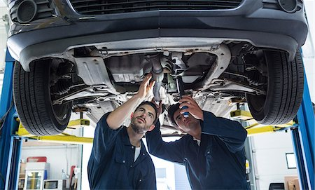 Mechanics examining silencer of a car using flashlight Stock Photo - Premium Royalty-Free, Code: 6109-08537757