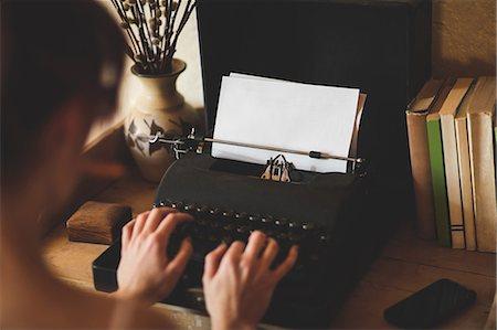 Young woman using typewriter Stock Photo - Premium Royalty-Free, Code: 6109-08537786
