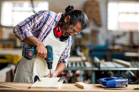 Carpenter drilling a hole in a wooden plank Stock Photo - Premium Royalty-Free, Code: 6109-08537950