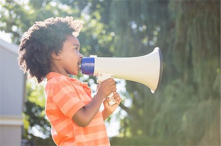 Cute mixed-race boy speaking on a megaphone Stock Photo - Premium Royalty-Free, Code: 6109-08538178