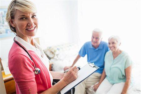 rehabilitation - Nurse writing on clipboard and senior couple sitting on a bed Stock Photo - Premium Royalty-Free, Code: 6109-08538293