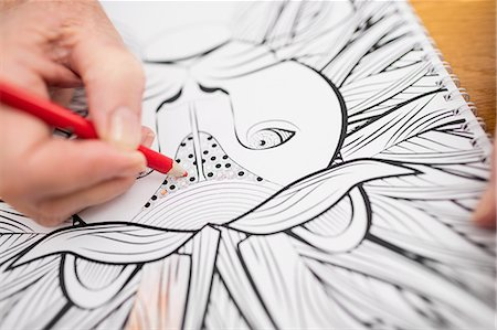 Senior woman colouring in a colouring book Stock Photo - Premium Royalty-Free, Code: 6109-08538201