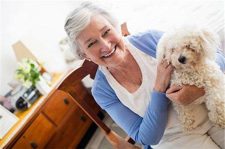Senior woman holding a dog Stock Photo - Premium Royalty-Free, Code: 6109-08538235