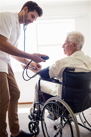 Nurse measuring the blood pressure of a senior man Stock Photo - Premium Royalty-Free, Code: 6109-08538342