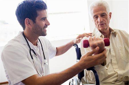 Nurse helping senior man with doing exercises Stock Photo - Premium Royalty-Free, Code: 6109-08538344