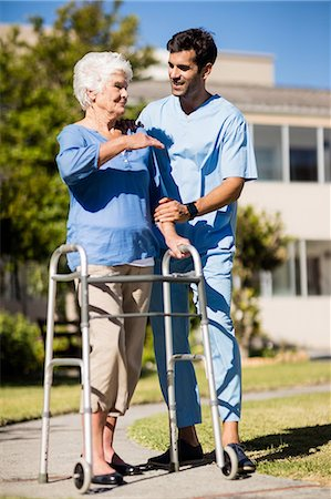 Nurse pushing the senior womans Zimmer frame Stock Photo - Premium Royalty-Free, Code: 6109-08538450