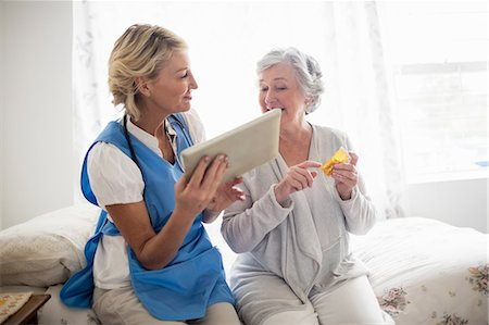Nurse showing a tablet to a senior woman Stock Photo - Premium Royalty-Free, Code: 6109-08538481