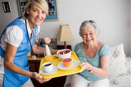 Nurse giving food to a senior woman Stock Photo - Premium Royalty-Free, Code: 6109-08538487