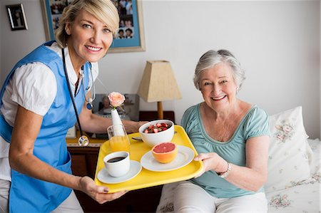 Nurse giving food to a senior woman Stock Photo - Premium Royalty-Free, Code: 6109-08538487