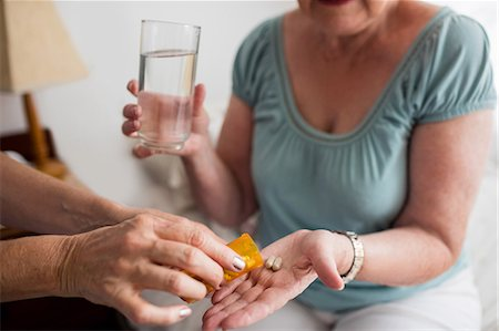 Nurse giving medicaments to a senior woman Stock Photo - Premium Royalty-Free, Code: 6109-08538489