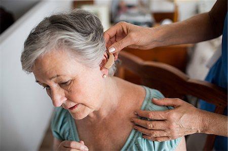 Nurse putting hearing aid to a senior woman Stock Photo - Premium Royalty-Free, Code: 6109-08538493