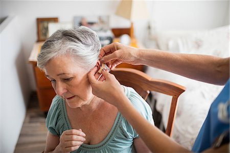 Nurse putting hearing aid to a senior woman Stock Photo - Premium Royalty-Free, Code: 6109-08538492