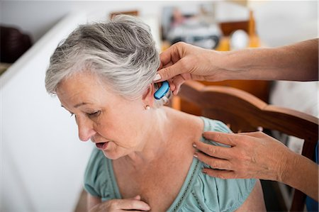Nurse putting hearing aid to a senior woman Stock Photo - Premium Royalty-Free, Code: 6109-08538494