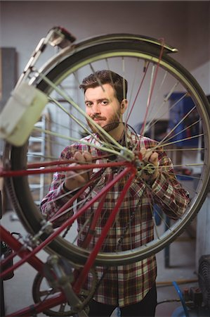 Portrait of smiling mechanic repairing a bicycle in workshop Stock Photo - Premium Royalty-Free, Code: 6109-08689850