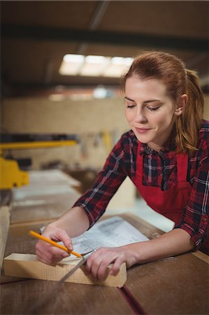 Female carpenter marking on wooden plank with pencil in workshop Stock Photo - Premium Royalty-Free, Code: 6109-08689905