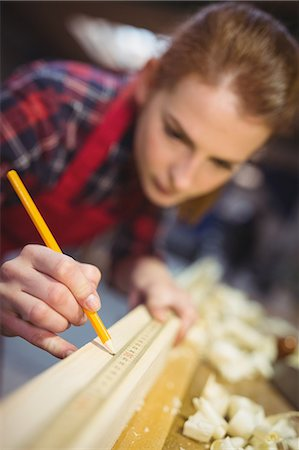 Female carpenter marking on wooden plank with pencil in workshop Stock Photo - Premium Royalty-Free, Code: 6109-08689920