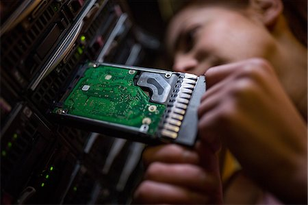 professional (pertains to traditional blue collar careers) - Close-Up of technician inserting a hard disk drive into a blade server in server room Stock Photo - Premium Royalty-Free, Code: 6109-08690053