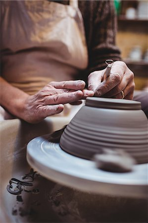 Midsection of craftsman making ceramic container in workshop Stock Photo - Premium Royalty-Free, Code: 6109-08690177