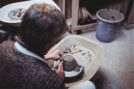 Rear view of craftsman preparing ceramic container in workshop Stock Photo - Premium Royalty-Free, Code: 6109-08690178