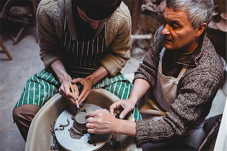 Mature craftsman discussing with colleague while working in workshop Stock Photo - Premium Royalty-Free, Code: 6109-08690183