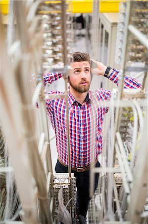 Technician getting stressed over server maintenance in server room Stock Photo - Premium Royalty-Free, Code: 6109-08690127