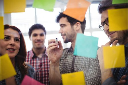 Businessman with coworkers looking at sticking notes on glass in office Stock Photo - Premium Royalty-Free, Code: 6109-08690284