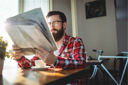 simsearch:6109-08700445,k - Young hipster customer reading newspaper with coffee at cafe Stock Photo - Premium Royalty-Free, Code: 6109-08690368