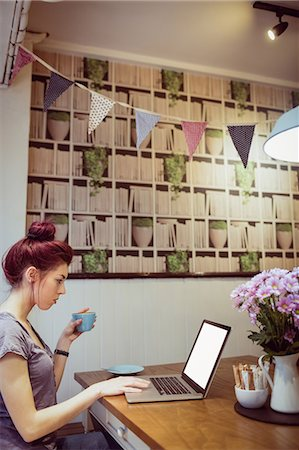 Hipster drinking a cup of coffee while using a laptop in a cafe Stock Photo - Premium Royalty-Free, Code: 6109-08690458