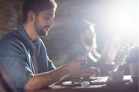 Side view of handsome young man using cellphone and laptop at cafe Stock Photo - Premium Royalty-Free, Code: 6109-08690411