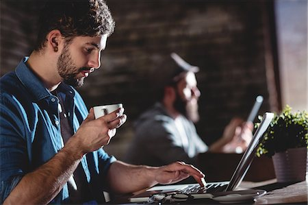 Side view of young man drinking fresh coffee while working on laptop at cafe Stock Photo - Premium Royalty-Free, Code: 6109-08690412